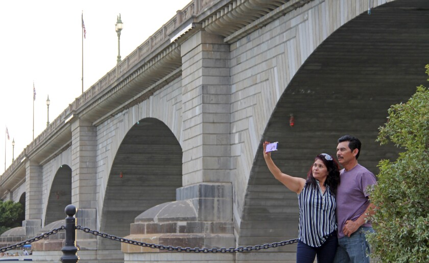 Claudia and Rafael Lopez take a selfie in front of the London Bridge in Lake Havasu City, Ariz., on Saturday, Sept. 25, 2021. Lake Havasu City is playing up its roots with a month of celebratory events marking the 50th anniversary of the dedication of the London Bridge after its piece-by-piece rebuild in the resort town along the Colorado River. (Daisy Nelson/Today's News-Herald/HavasuNews.com via The AP)
