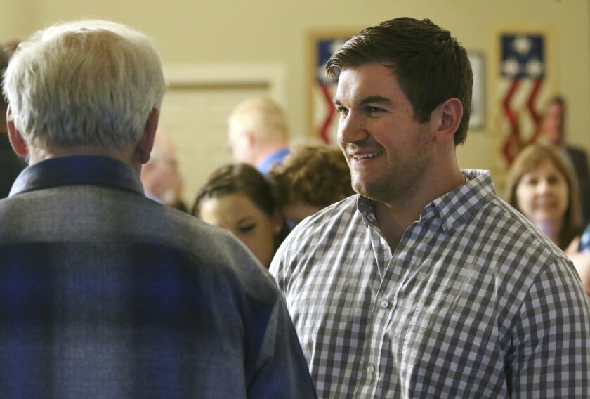 FILE - In this May 15, 2018 file photo, Alek Skarlatos, right, speaks at the Douglas County Republican Party headquarters in Roseburg, Ore. Skarlatos, who in 2015 helped thwart an attack by a gunman on a Paris-bound train, faces longtime Democratic U.S. Rep. Peter DeFazio in the November election. (Michael Sullivan/The News-Review via AP, File)