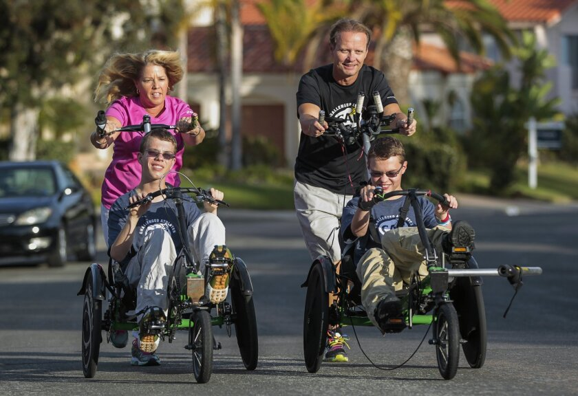 Jim and Lisa Pathman push their 16-year-old twin sons Shane, left, and Riley, who were born with cerebral palsy, as they demonstrate the racing chairs they will use so that all four of them can compete in an upcoming triathlon while in front of their home in Del Mar on Thursday.