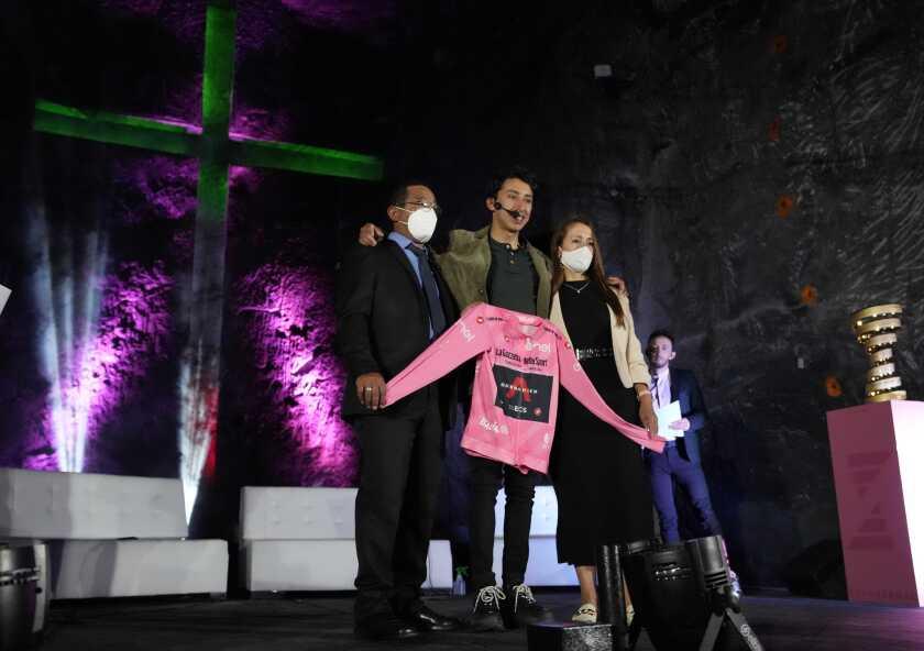 El ciclista colombiano Egan Bernal y sus padres posan para la foto durante la ceremonia de bienvenida en la Nueva Catedral de Sal en Zipaquirá, Colombia, sábado 19 de junio de 2021. Las autoridades y los fanáticos del ciclismo le dieron una recepción de héroe por su triunfo reciente en el Giro de Italia. (AP Foto/Fernando Vergara)