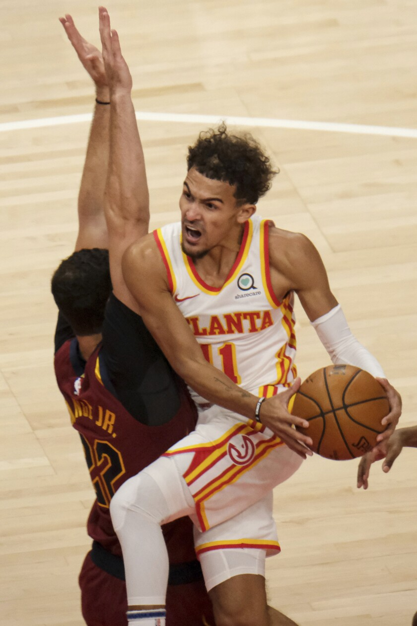 Atlanta Hawks guard Trae Young (11) drives past Cleveland Cavaliers forward Larry Nance Jr. (22) during the first half of an NBA basketball game on Saturday, Jan. 2, 2021 in Atlanta. (AP Photo/Ben Gray)