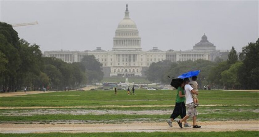 FILE -- In this Aug. 27, 2011 file photo, a family walks on the National Mall in Washington as Hurricane Irene approaches the Mid-Atlantic states. (AP Photo/Luis M. Alvarez)