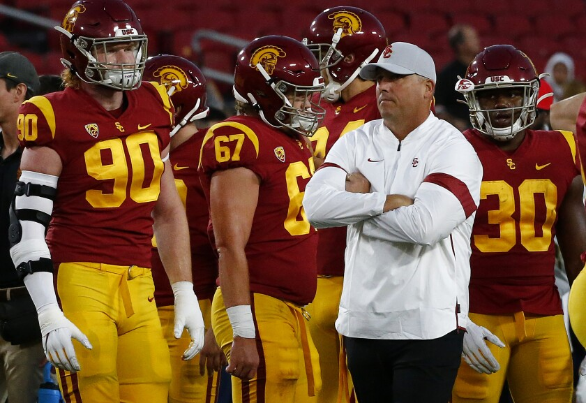 USC coach Clay Helton watches his team warm up before a game against Arizona at the Coliseum.