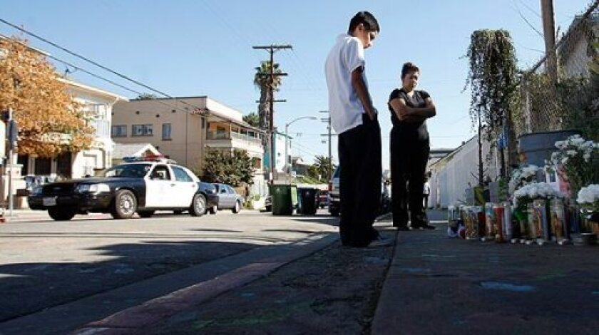An LAPD cruiser drives through the neighborhood south of Echo Park as Hugo Gonzalez, 12, a relative of the victim, and Kathy Morales, whose 16-year-old brother was killed last year nearby, stand in front of the memorial for Robert Lopez Jr.