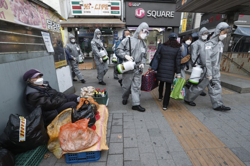 People in protective gear walk by a senior woman sidewalk vendor in Seoul, all wearing face masks.