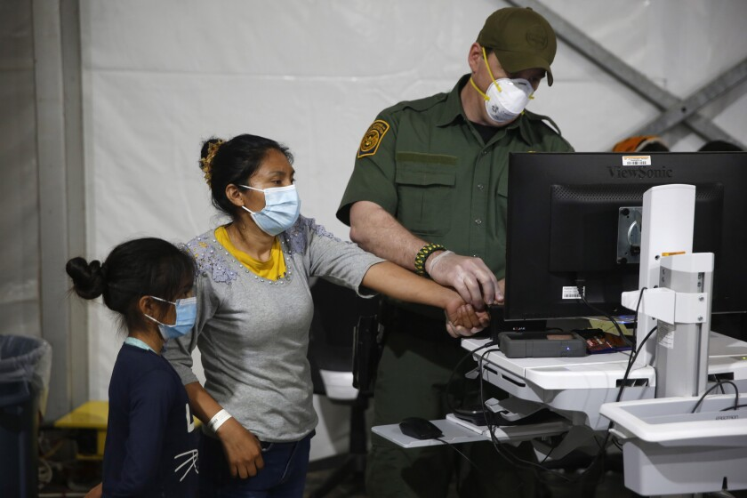 A woman and her daughter with a U.S. border official.