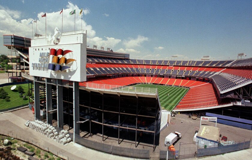 FILE - In this July 21, 2000, file photograph, clouds roll in over the original Mile High Stadium from the main concourse of the new stadium being built within a stone's throw of the venerable field in Denver. The demise of Sports Authority has reignited a fight in Colorado over the future of the D