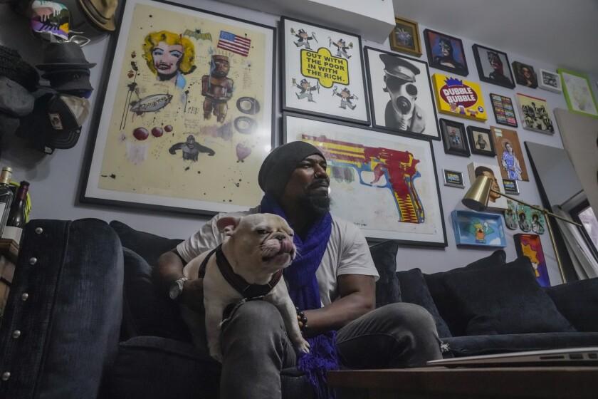 El pintor Guy Stanley Philoche y su perro Picasso fotografiados en el pequeño departamento del artista