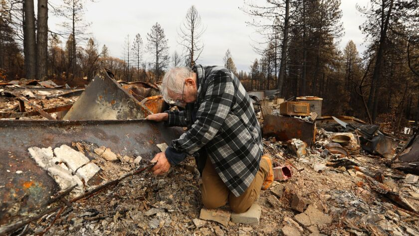 PARADISE, CALIFORNIA--DEC. 5, 2018--Kneeling in the ash of his home, Robert Wedman, age 83, found mo