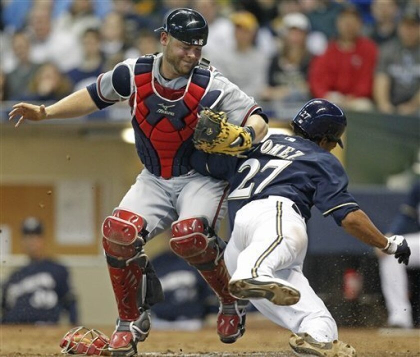 Atlanta Braves catcher Brian McCann, left, tags out Milwaukee Brewers' Carlos Gomez (27) at home plate in the fifth inning of a major league baseball game on Wednesday, April 6, 2011, in Milwaukee. (AP Photo/Jeffrey Phelps)