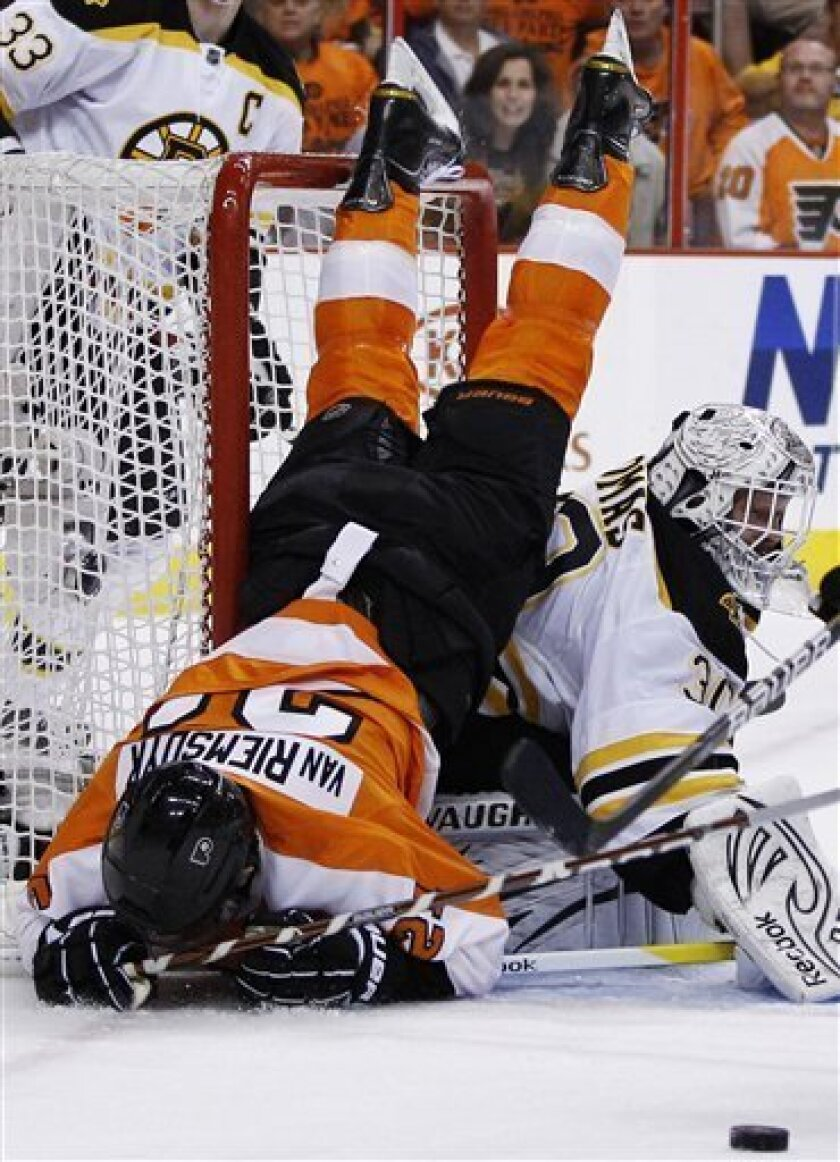 Philadelphia Flyers' James van Riemsdyk (21) tumbles over Boston Bruins goalie Tim Thomas (30) during the second period in Game 1 of the Eastern Conference semifinal NHL Stanley Cup playoffs series, Saturday, April 30, 2011, in Philadelphia. (AP Photo/Matt Slocum)