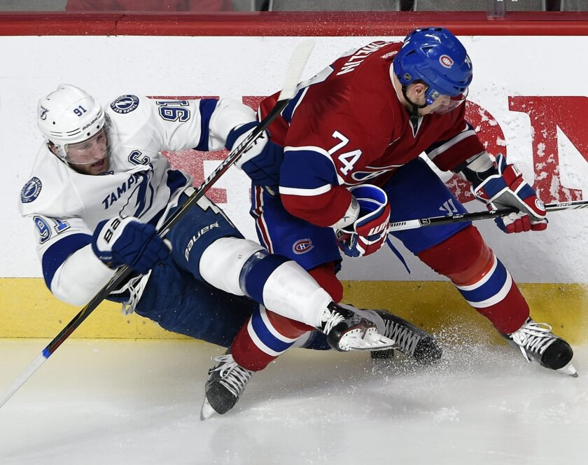 Tampa Bay Lightning center Steven Stamkos (91) is checked by Montreal Canadiens defenseman Alexei Emelin (74) during the second period of Game 1 of second-round playoff NHL hockey action Friday, May 1, 2015, in Montreal. (Ryan Remiorz/The Canadian Press via AP) MANDATORY CREDIT