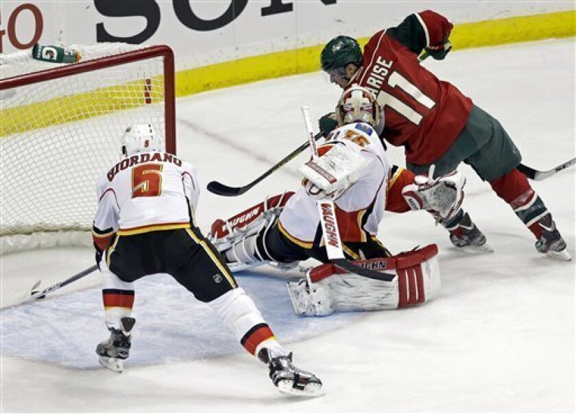 Minnesota Wild's Zach Parise, right, shoots the puck past Calgary Flames goalie Joey MacDonald in the first period of an NHL hockey game Tuesday, Feb. 26, 2013, in St. Paul, Minn. The goal call was reversed by officials upon review. At left is Flames' Mark Giordano. (AP Photo/Jim Mone)