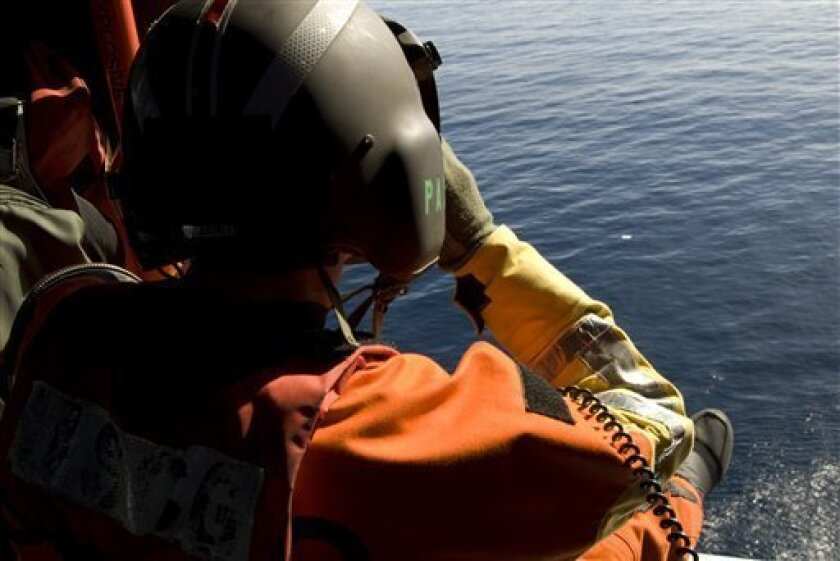 This image provided by the U.S. Coast Guard shows a Coast Guard aircrew member from Sector San Diego conducting search patterns east of San Clemente Island Friday, Oct. 30, 2009 to search for survivors of a mid-air collision that occurred Thursday. The collision occurred between a Coast Guard HC-130 Hercules and a Marine AH-1 Super Cobra.(AP Photo/U.S Coast Guard, Petty Officer 3rd Class Cory J. Mendenhall)