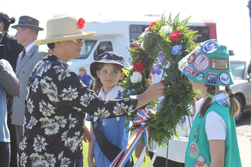 Song Pak places a flower in honor of all veterans, but specifically her husband, who served in multiple wars and who also attended the La Jolla ceremony.