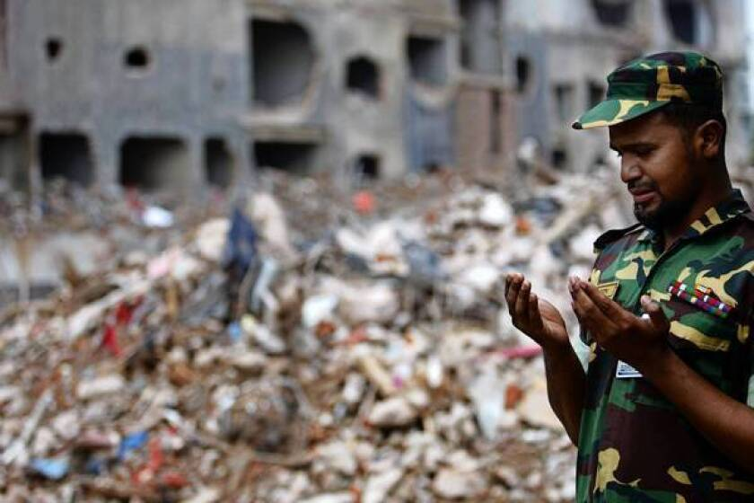 A Bangladeshi soldier takes part in prayers at the site of a collapsed garment factory outside Dhaka, the capital. The military ended its rescue and cleanup operation and turned responsibility over to civilian authorities.