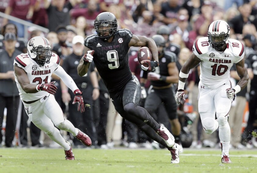 Texas A&M wide receiver Ricky Seals-Jones (9) cuts upfield after a pass reception as South Carolina safety Isaiah Johnson (21) and linebacker Skai Moore (10) pursue him during the first half of an NCAA college football game, Saturday, Oct. 31, 2015, in College Station, Texas. (AP Photo/Eric Gay)