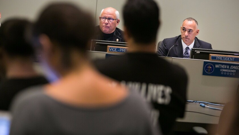 Police Commission President Matt Johnson, right, and Vice President Steve Soboroff listen to a speaker at a meeting last fall.