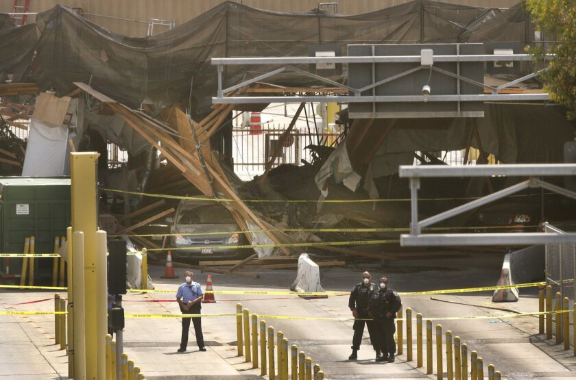 Vehicles can be seen under the collapsed overhead construction canopy at the San Ysidro border crossing that collapsed Wednesday morning. Eleven people were hospitalized and about a dozen more were being evaluated for possible injuries following the collapse. — Howard Lipin