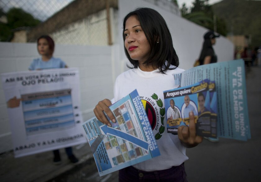 In this Tuesday, Nov. 10, 2015photo, a supporter holds political propaganda of opposition candidate Ismael Garcia, from the MUD Unity party, holds a poster explaining how to mark a vote for him for the upcoming Congressional elections as he visits houses in Maracay, Venezuela. Voters in this industrial state are gearing up to choose between two Congressional candidates both are named Ismael Garcia. The result has been a bizarre campaign in which political veteran Ismael Garcia is mostly focused on helping voters identify him correctly when they go to the polls. (AP Photo/Ariana Cubillos)
