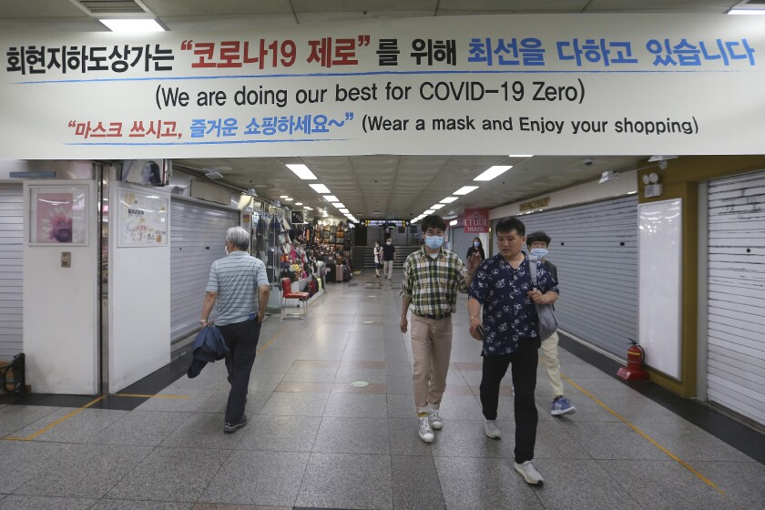 People walk through an underground shopping mall in Seoul, South Korea, Thursday, June 11, 2020. Just weeks ago South Korea was celebrating its hard-won gains against the coronavirus. It was easing social distancing measures, reopening schools and promoting its tech-driven methods of fighting the spread of the virus. But the country's success story is being threatened by a resurgence of infections in the area around Seoul where half of South Korea's 51 million people live. (AP Photo/Ahn Young-joon)