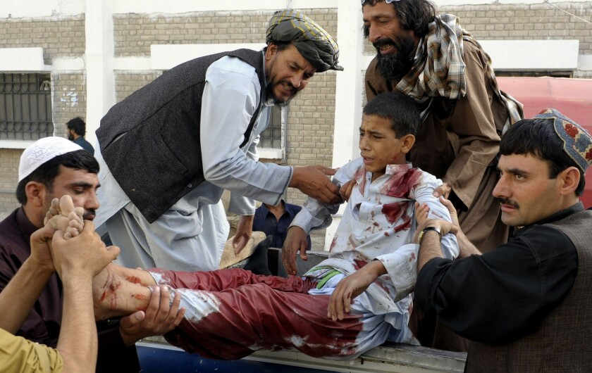 Men carry an injured youth outside a hospital following a shooting attack in the Pakistani city of Quetta.