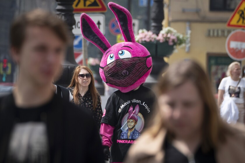 A person dressed as a bunny and wearing a funny face mask advertises a store amid the ongoing COVID-19 pandemic in St. Petersburg, Russia, Wednesday, June 10, 2020. (AP Photo/Dmitri Lovetsky)