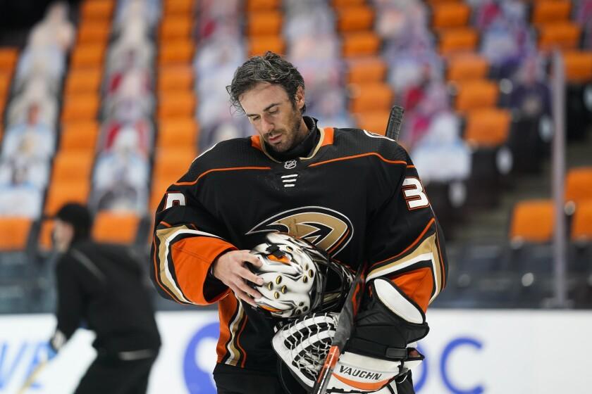 Ducks goaltender Ryan Miller takes off his mask.
