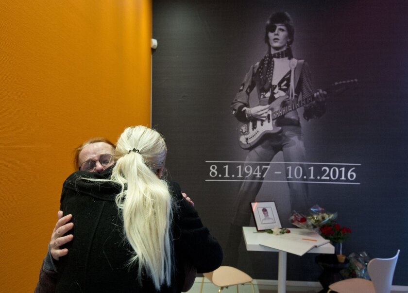 """A crying woman, left, is comforted after signing a book of condolences for pop star David Bowie at the Groninger Museum, which is hosting the """"David Bowie Is..."""" exhibition."""