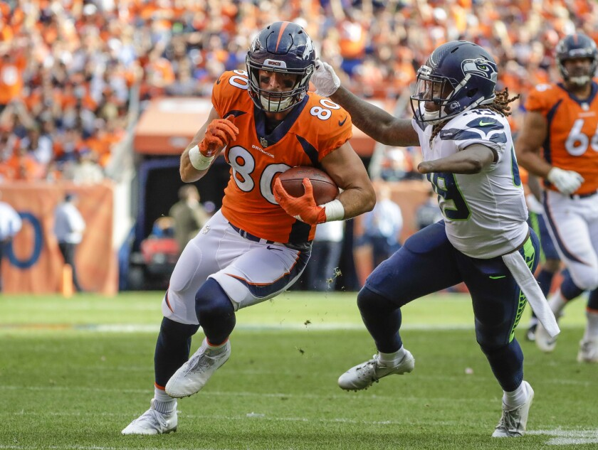 FILE - In this Sept. 9, 2018, file photo, Denver Broncos tight end Jake Butt (80) runs against Seattle Seahawks linebacker Shaquem Griffin (49) during the second half of an NFL football game in Denver. Butt, the once-promising tight end whose football career was waylaid by six knee operations, announced his retirement from the NFL on Thursday, July 29, 2021, saying he could no longer hide the fact that he'd lost his passion for the game he loves. (AP Photo/Jack Dempsey, File)