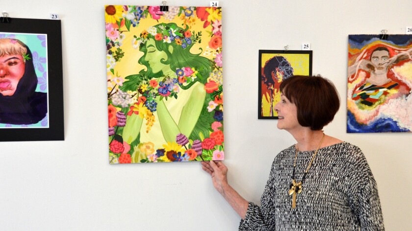 Furnishing Hope founder Beth Phillips displays student artwork from the Congressional Art Competition in the new Furnishing Hope Gallery in Newport Beach.