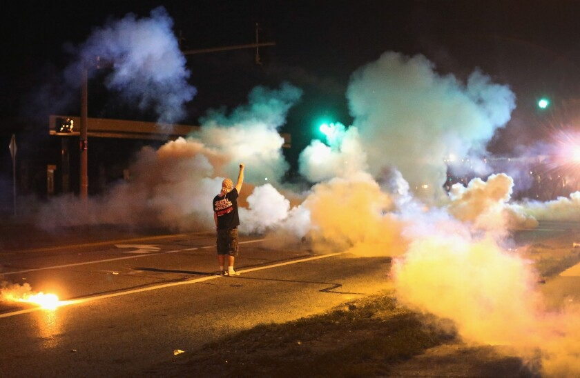 A demonstrator, protesting the shooting death of Michael Brown, stands his ground as police fire tear gas Wednesday night in Ferguson, Mo.