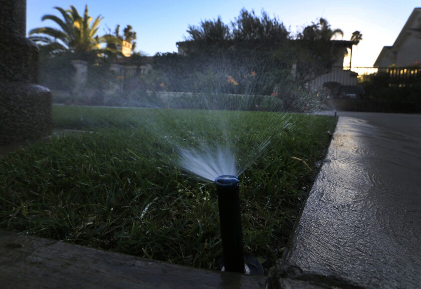 Sprinklers water a lawn at dusk in Beverly Hills. Statewide, Californians cut their urban water use in March by 24.3% compared with the same month in 2013, regulators said.