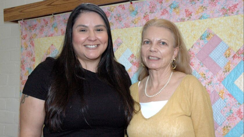 Scholarship recipient Melissa Ramos, left, is congratulated by Susan Edwards, president of the Women