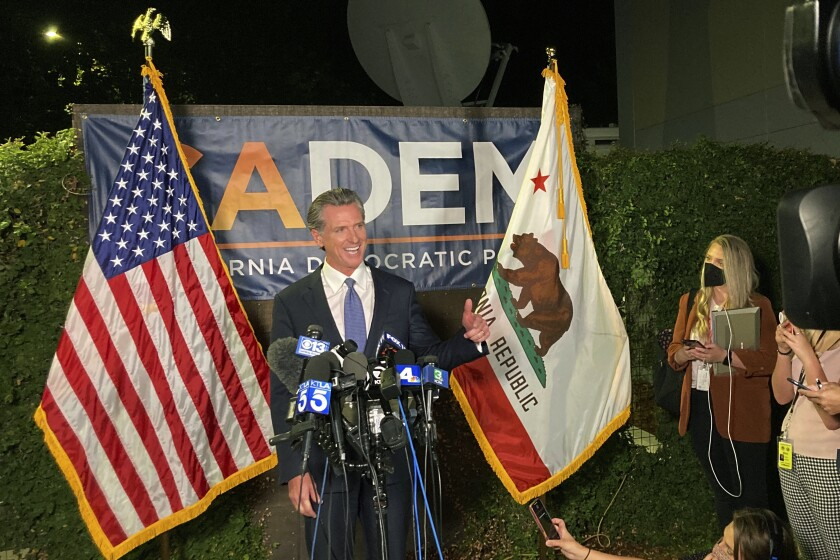 Gov. Gavin Newsom, flanked by flags, speaks into microphones