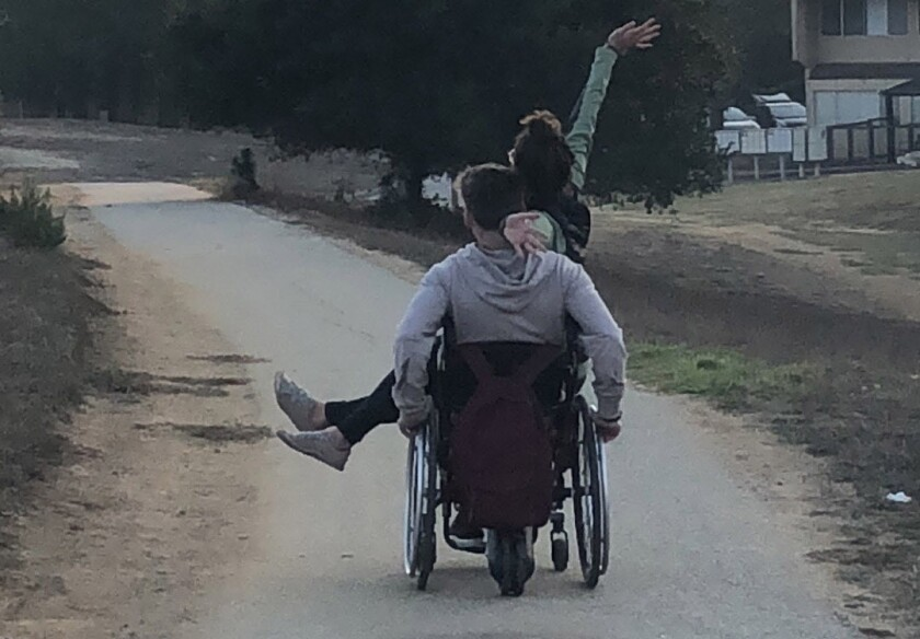 Tanner Cislaw and his girlfriend, Isabella Dean, take a ride in his wheelchair on the campus of UC S