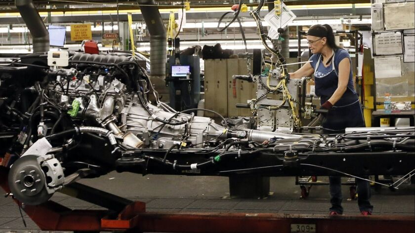 FILE - In this July 14, 2015 file photo, an employee works on the assembly line at the General Motor