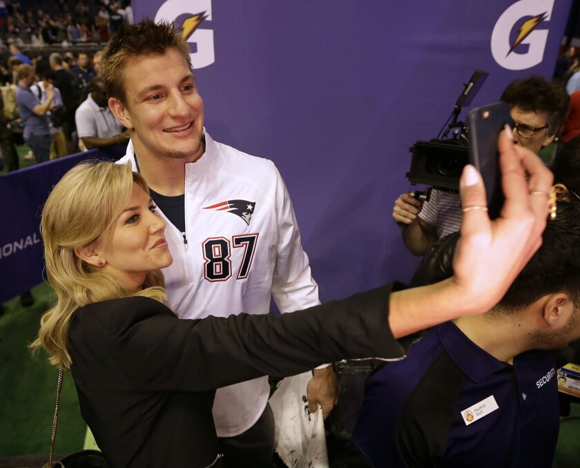 FILE - In this Jan. 27, 2015, file photo, New England Patriots' Rob Gronkowski poses for a selfie with television host and sportscaster Charissa Thompson during media day for NFL Super Bowl XLIX football game in Phoenix. Men are behind more news stories than women by a nearly 2-to-1 margin across p
