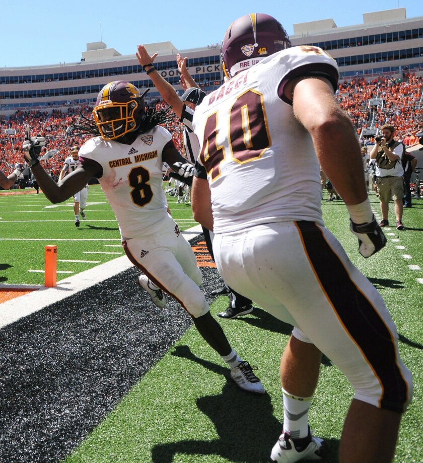 A referee signals a touchdown as Central Michigan wide receiver Corey Willis (8) celebrates with his teammate running back Joe Bacci (40) after scoring the winning touchdown in the final seconds of an NCAA college football game between against Oklahoma State in Stillwater, Okla., Saturday, Sept. 10