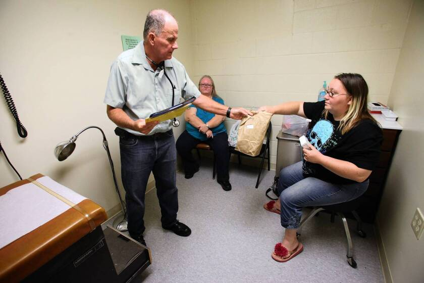 Dr. Dalton McInnis, medical director of Baptist Mission Center Clinic in Oklahoma City, gives medication to patient Jaclyn Leathers. Leathers and her mother, Bonnie Mize, in background, are both uninsured. The new healthcare law is a tough sell in Oklahoma.