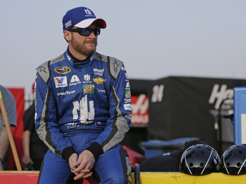 Dale Earnhardt Jr sits on a pit road wall before qualifying for Sunday's NASCAR Sprint Cup series auto race at Charlotte Motor Speedway in Concord, N.C., Thursday, May 26, 2016. (AP Photo/Chuck Burton)