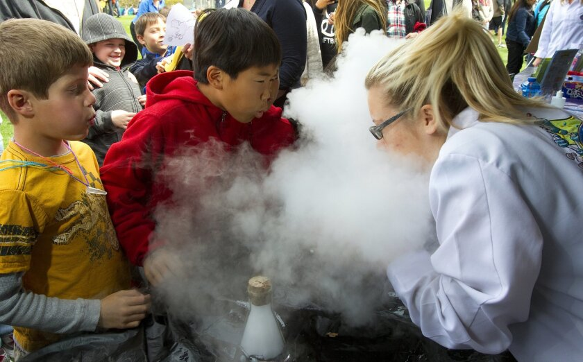 Mathew Enos (left) and Allen Tu help Emily Brown blow away the carbon dioxide that was produced from adding dry ice to water. The boys were at the Mad Science booth at San Diego Festival of Science & Engineering at Petco Park in 2012. u-t file