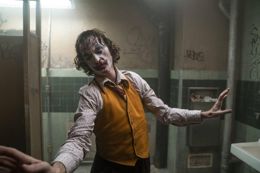 "Joaquin Phoenix as the ""Joker"" in a public restroom with graffiti on the walls."