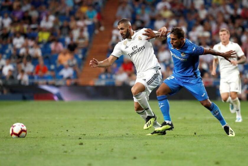 El delantero francés del Real Madrid Karim Benzema (i) lucha con el uruguayo Damián Suárez, del Getafe CF, durante un partido. EFE/Archivo
