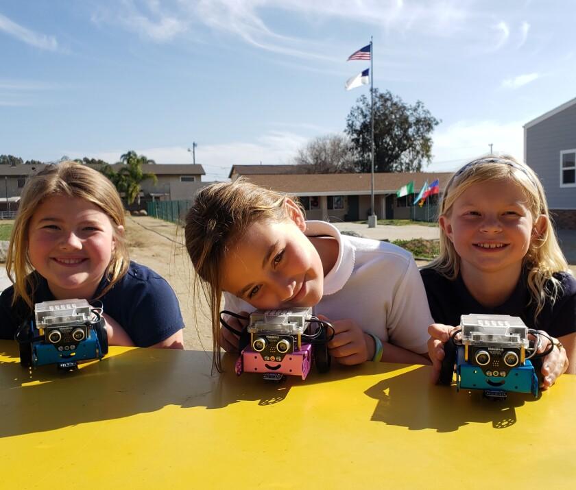 Three happy third-graders with their STEM program robots.