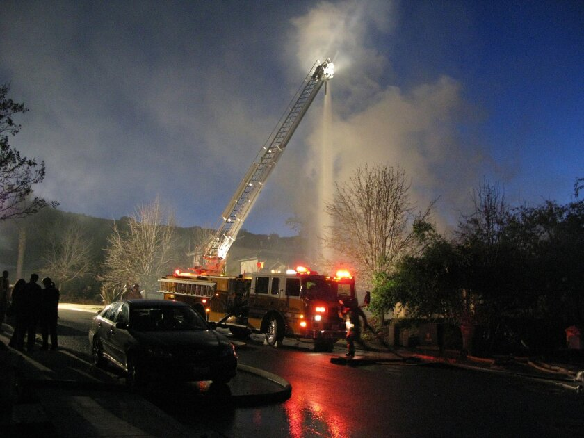 Santee firefighters continued to pump water onto the Clifford Heights home Saturday evening.