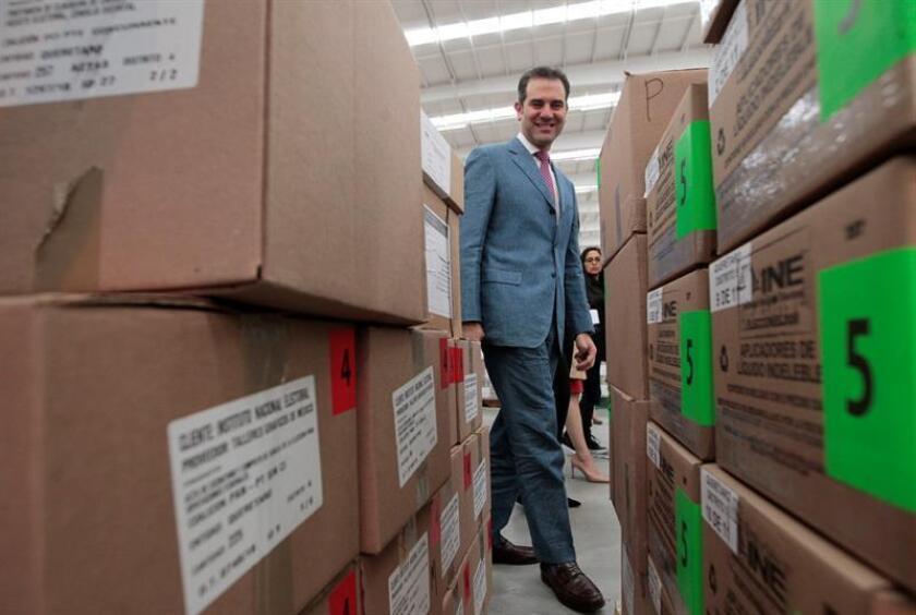 El consejero presidente del Instituto Nacional Electoral (INE), Lorenzo Córdova (c), muestra a los medios las miles de cajas que contienen las millones de boletas electorales que el Instituto Federal Electoral comenzó a distribuir hoy, viernes 1 de junio de 2018, desde el municipio de Tepotzotlán, en el estado de México (México). EFE