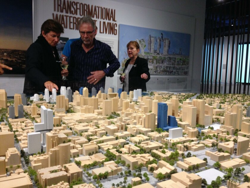 Visitors to the Pacific Gate sales office at First Avenue and G Street study a model of downtown with Bosa Development's planned projects in blue.