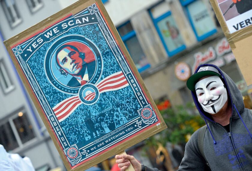A demonstrator holds a placard with a picture of President Obama at a protest against U.S. intelligence programs in Hanover, Germany.
