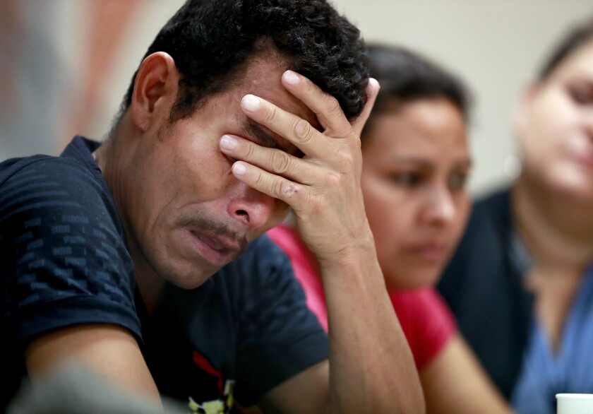 Melvin and Iris, both from Honduras, listen to stories about border separation.